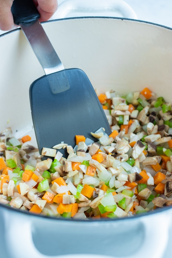 The chopped vegetables are sautéed in a pan on the stove.