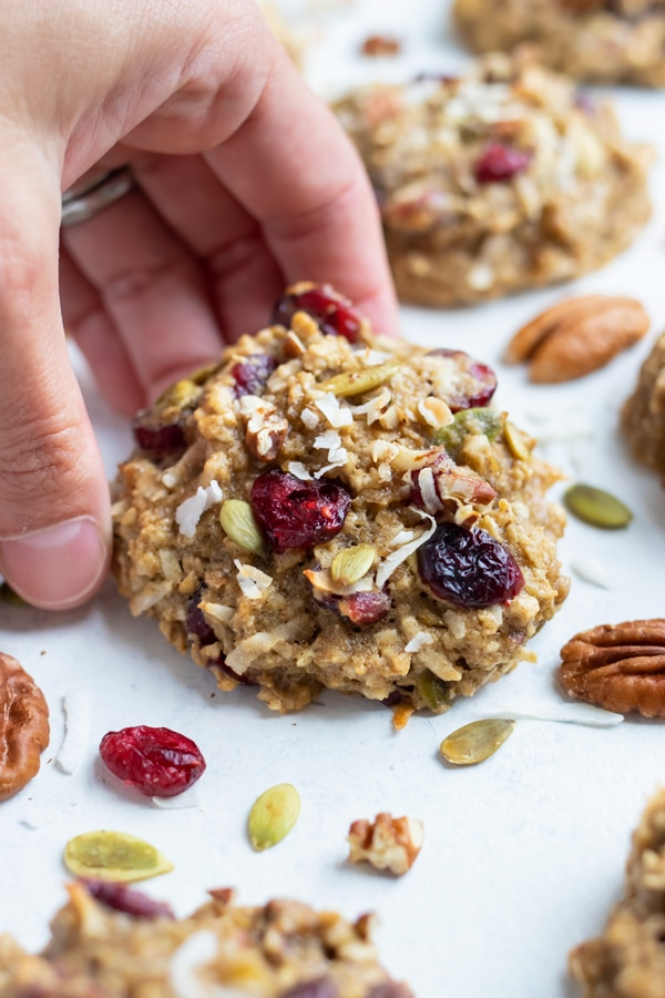 A cookie is lifted up by a hand for a healthy snack.