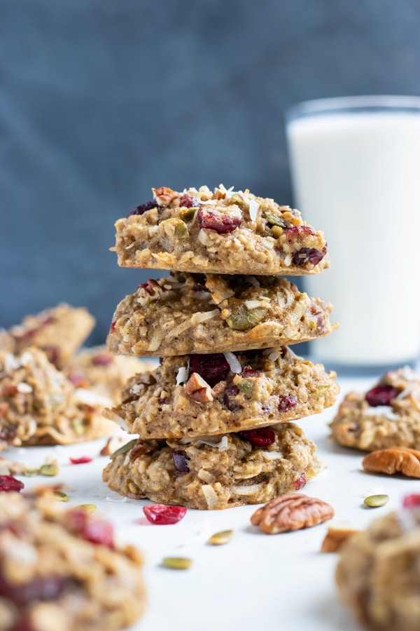 Oatmeal breakfast cookies are shown in a stack with a glass of milk.