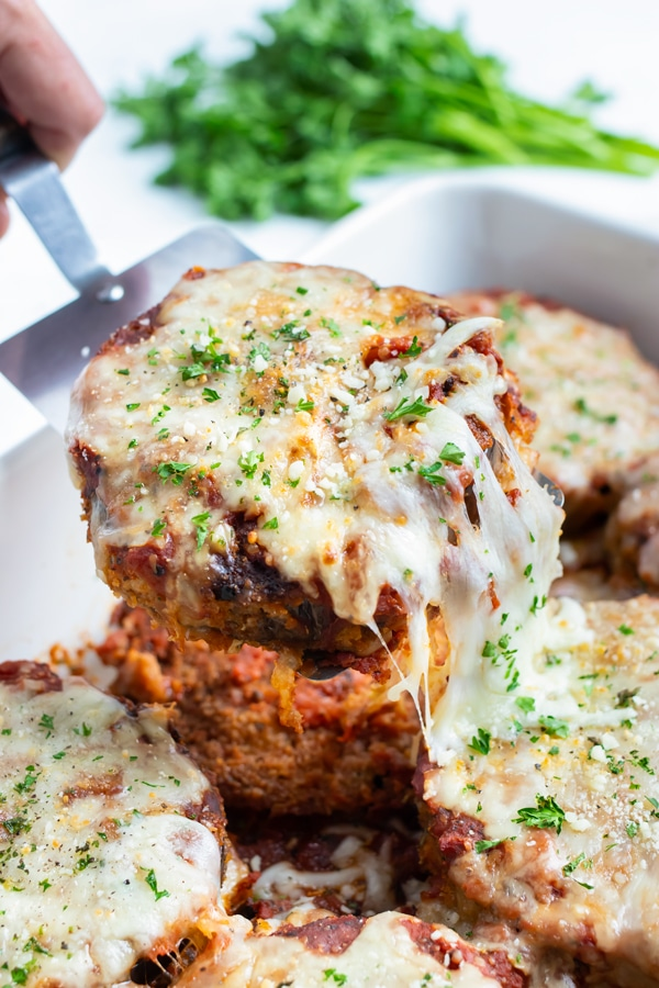Eggplant parmesan is served with a spatula.