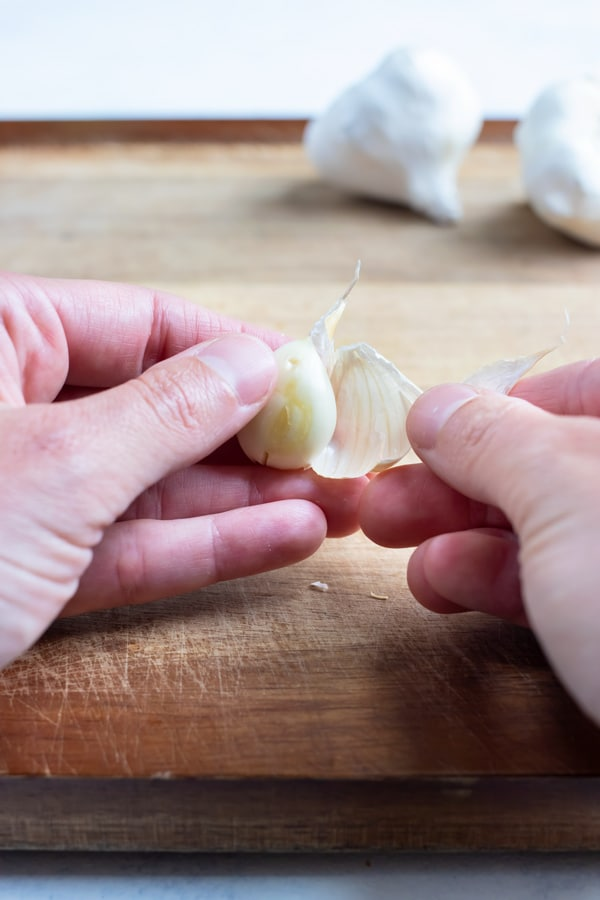 Garlic clove is peeled with your hands.