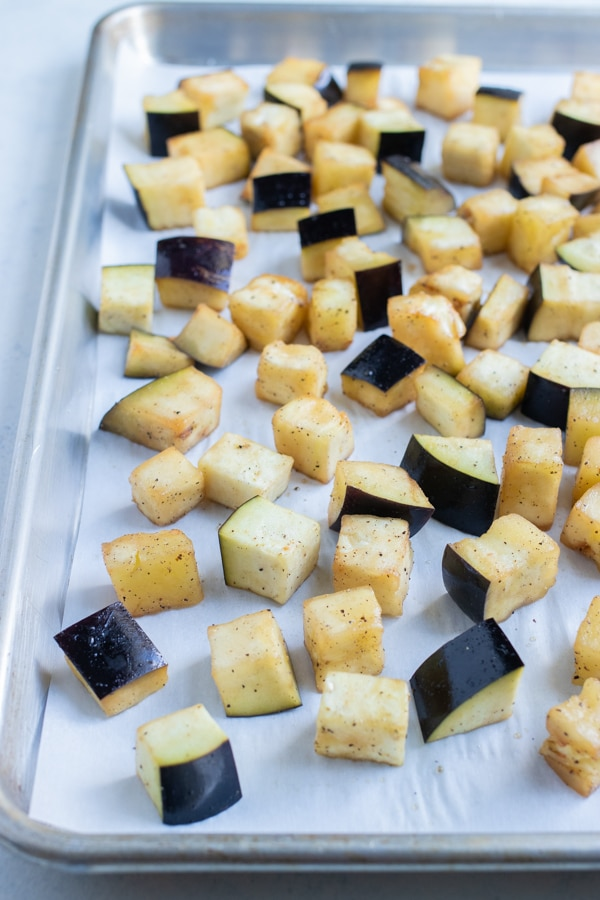 Eggplant cubes are laid flat on a baking sheet.