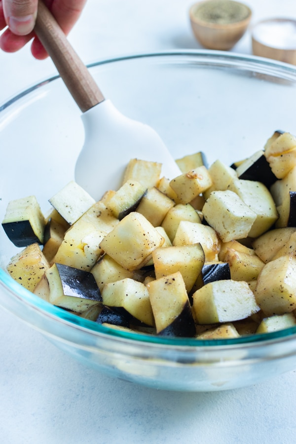 Cubed eggplant is covered in oil in a bowl.