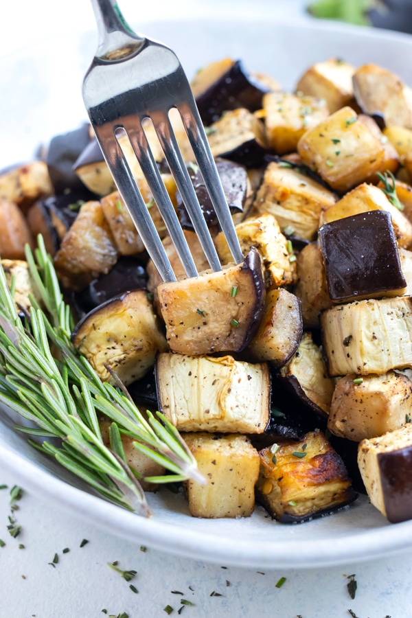 A fork is used to eat the roasted eggplant.