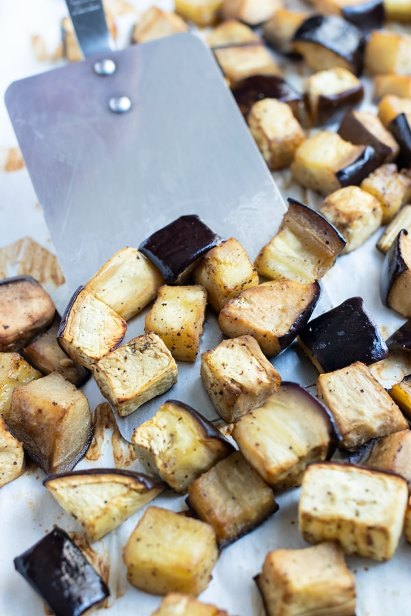 The cubed roasted eggplant is removed from the baking sheet.
