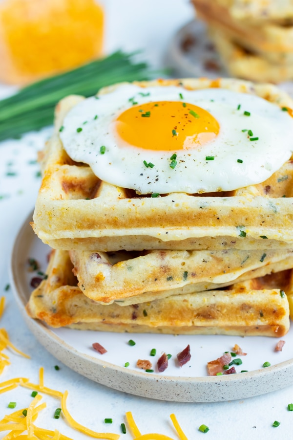 Savory waffles are stacked together on a plate for a filling breakfast recipe.