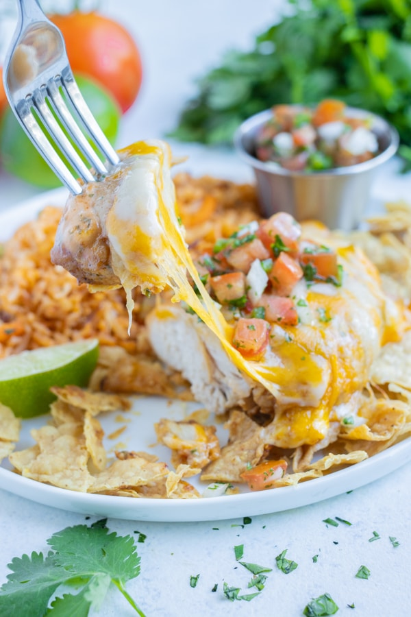 Cheesy Mexican chicken is eaten with a fork.