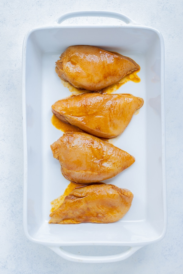 Marinated chicken breasts are laid flat in a baking dish.