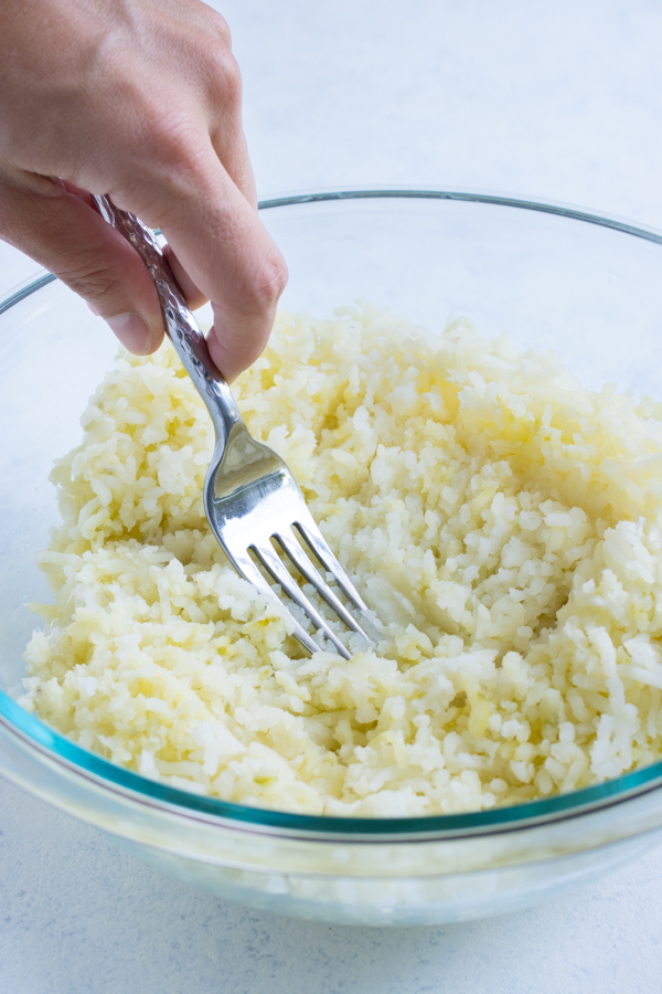 Potatoes are mashed with a fork in a glass bowl.