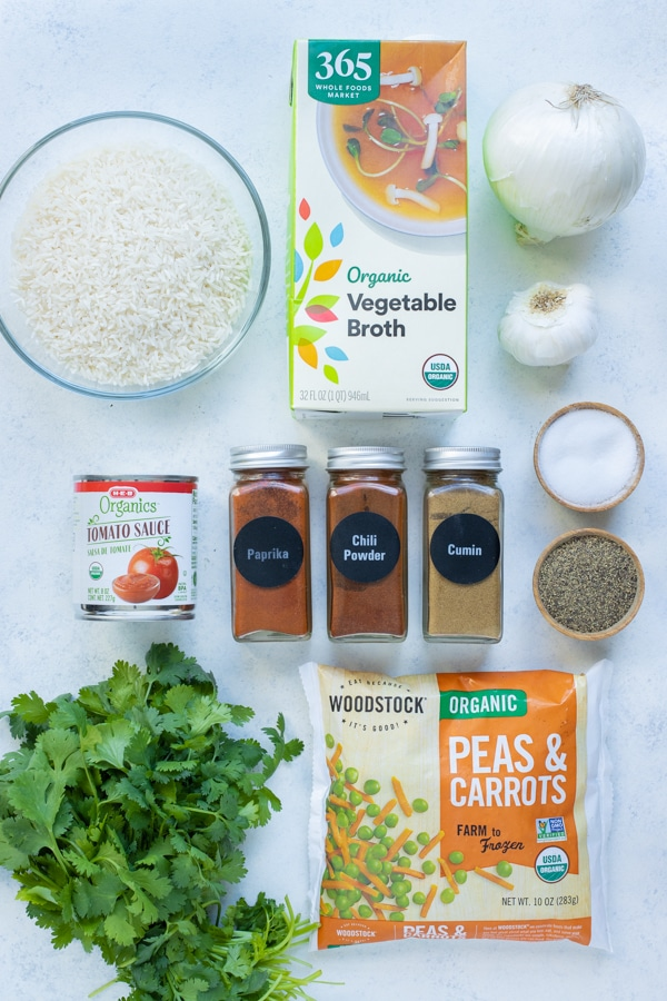 Spices, rice, onion, garlic, vegetable broth, peas and carrots, canned tomatoes, and cilantro are the ingredients for this recipe.