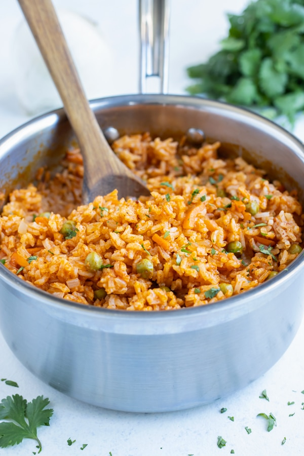 Homemade Mexican rice is dished with a wooden spoon from a pot.