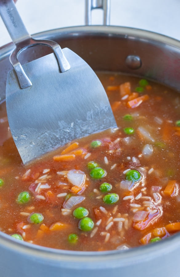 Broth, tomatoes, peas, carrots, and rice are added to the pot.
