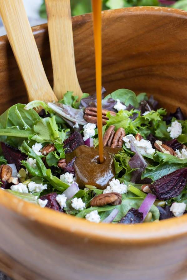 A homemade vinaigrette is poured over a large bowl of holiday salad.