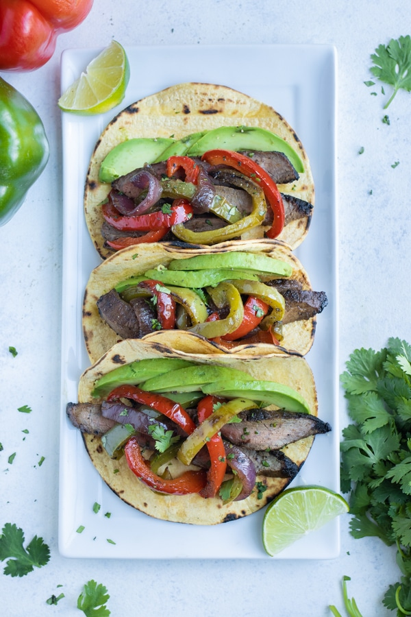 Steak fajitas are lined up on a plate with fresh lime juice.