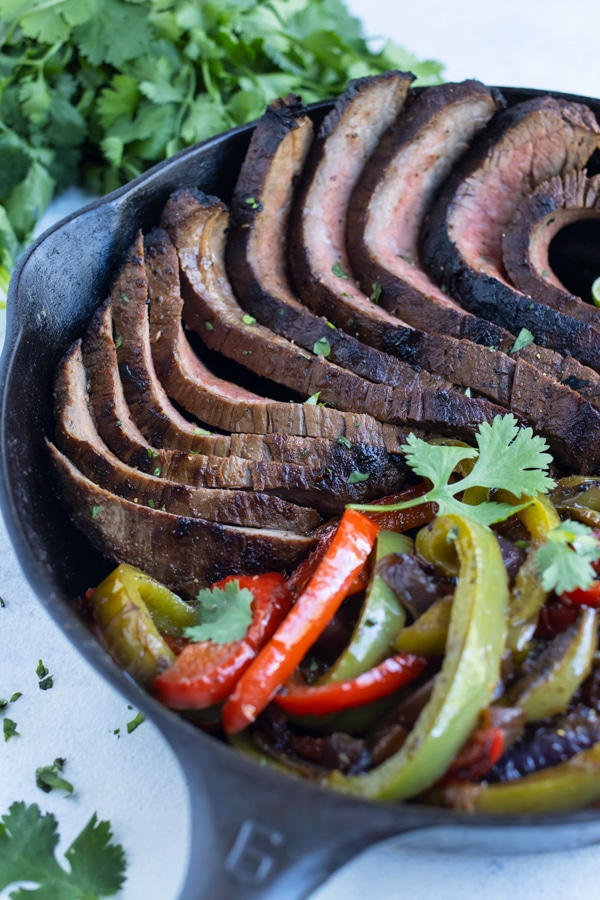 Easy steak fajitas are served from a cast iron skillet.