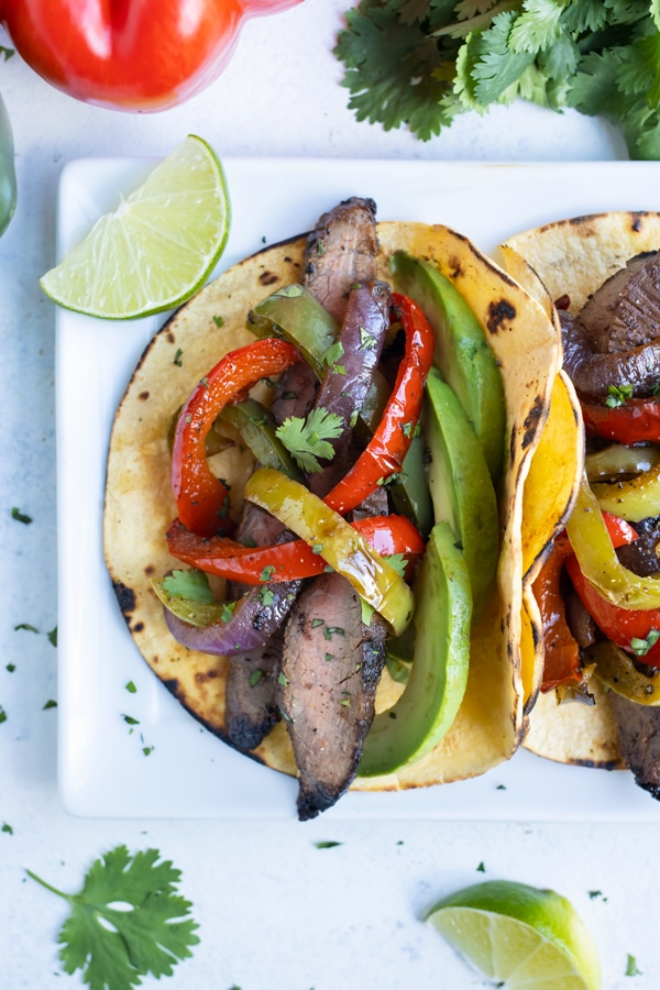 Corn tortillas are loaded with steak and vegetables.