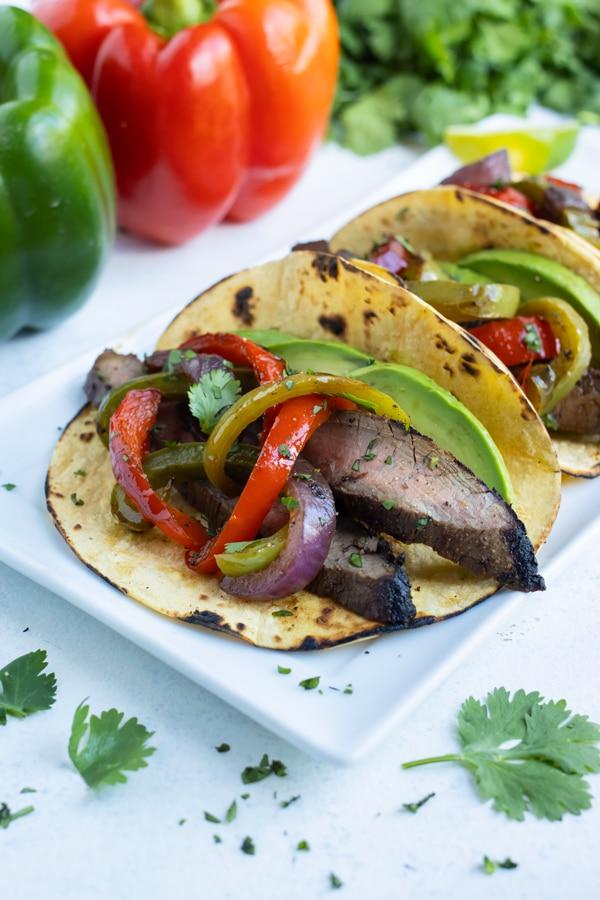 Three steak fajitas are served on a white platter.