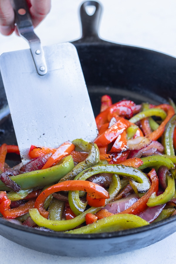 The vegetables are sautéed in a pan on the stove.