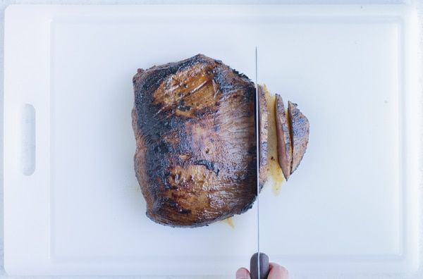The cooked steak is sliced on top of a cutting board.
