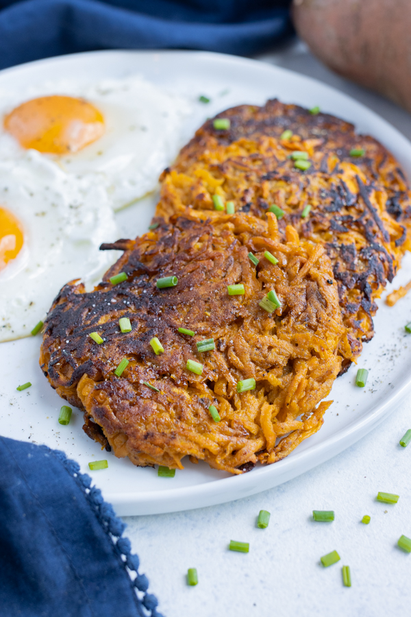 Crispy hash browns are served with fried eggs on a plate.