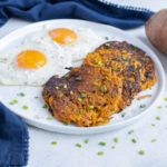 A plate of eggs and sweet potato hash browns is set on the counter.
