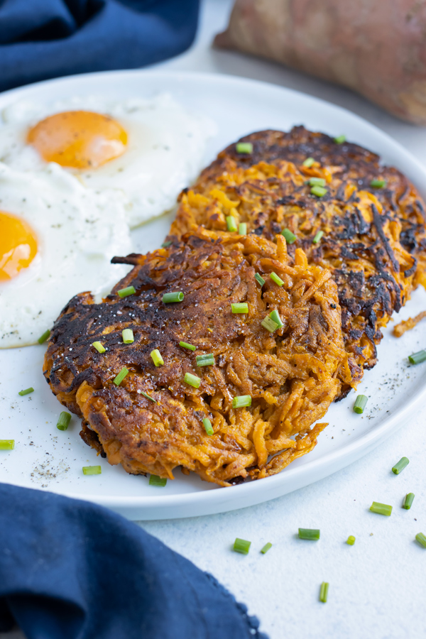 Whole30 sweet potato hash browns are served with eggs for a healthy meal.