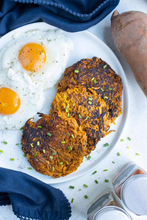 Two eggs are plated with three crispy sweet potato hash browns.
