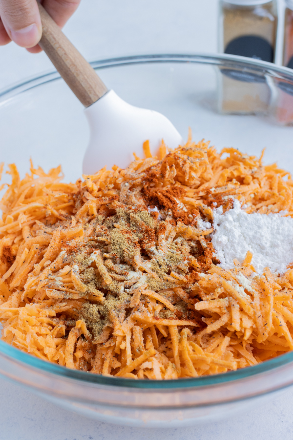 Seasonings and flour are mixed into the sweet potatoes.