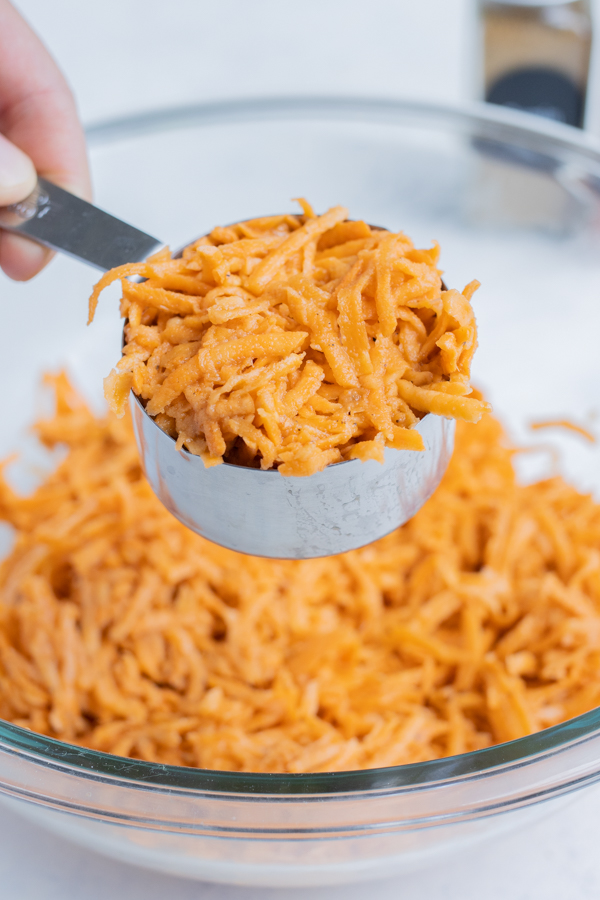 The sweet potato hash brown mixture is measured out before cooking.