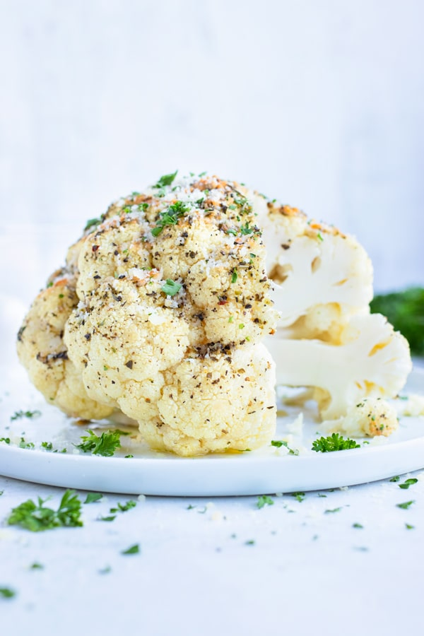 Whole roasted cauliflower head with parmesan and garlic on a white plate to be served for dinner.