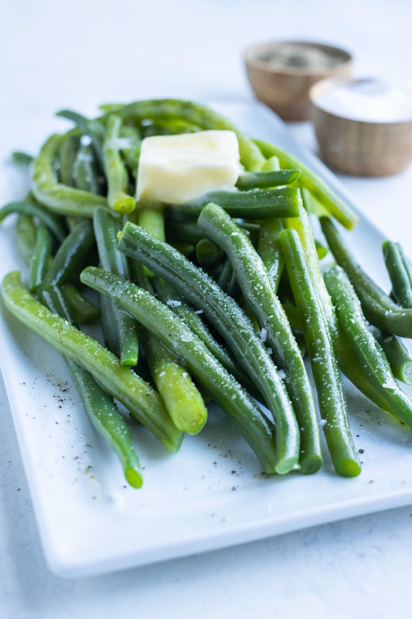 Boiled green beans shown on a plate with butter, salt, and pepper.