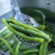 Beans are boiled in a pot of water.
